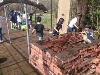 たくさんあるレンガを、どんどん積んでいく。間に泥を塗っていくのを思いついたのも、子どもたちです。