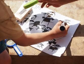 どんどん人を描いて、お日様で目鼻のかたちに穴をあけてます。